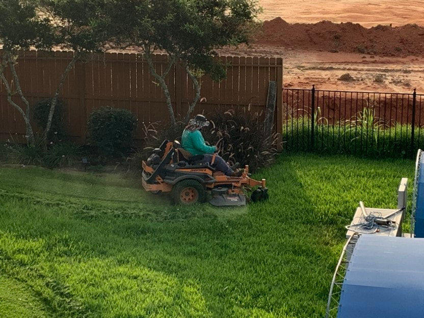 Picture of a Lawn Care Service man on a zero turn mower cutting grass in a townhouse complex near boat docks.