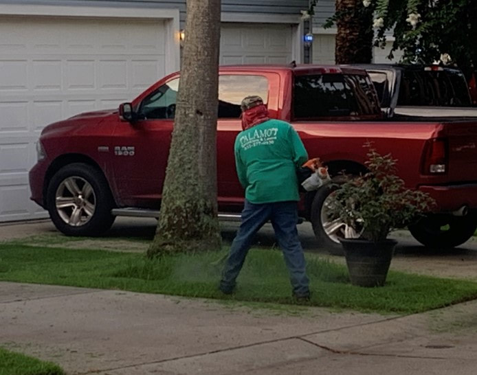 Lawn Care Man using a string trimmer to edge the grass along a curb in a townhouse complex